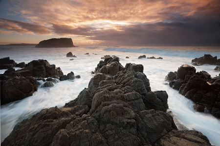 kiama: Ocean flows around the Minnamurra volcanic rock outcrop and views across to Stack Island formerly an extension of the rocks and cliffs here..  Taken at low tide during sunrise
