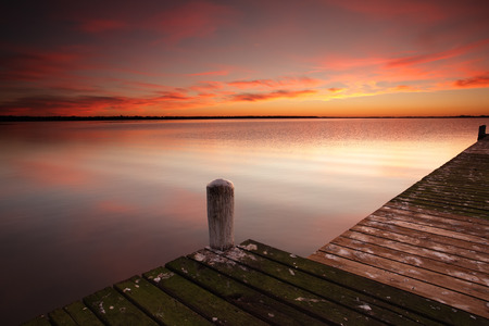 Glorious red sunrise skies and water reflections from one of the jetties at Berkeley Vale on the Central Coast of NSW Australia