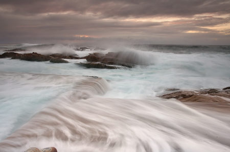 overflows: Moodly sunrise and enormous swell nd tide creating ocean overflows and fast flowing water of the rockpool
