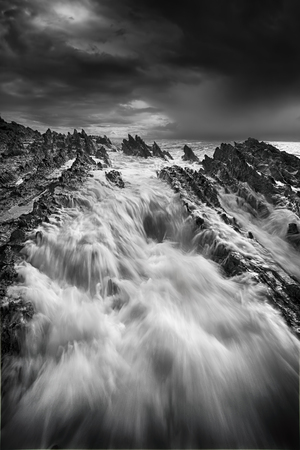 inhospitable: Storm approaching and rough seas with big flows over jagged deathly rocks