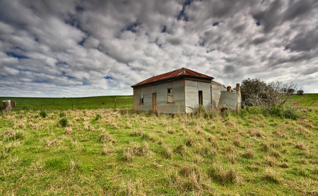 Abandoned farm homstead with corrugated iron roof and walls and boarded up windows left to the elements and now in disrepair