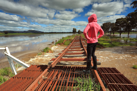 nsw: A female looks out over the floodwaters from the buckled train tracks at Crowther, Hilltops Region, Country NSW. Stock Photo