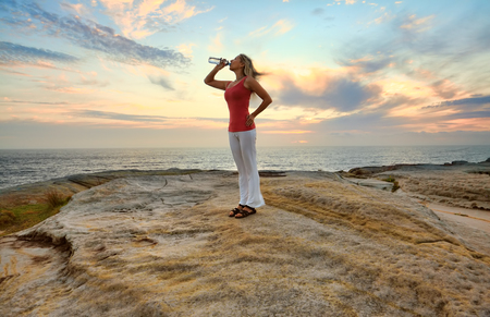 health and fitness: Female drinking bottled water outdoors by the ocean with pretty sky behind her