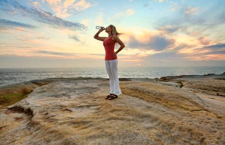 forme et sante: Femme de boire l'eau en bouteille à l'extérieur par l'océan avec un joli ciel derrière elle