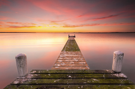 jetty: Sunrise colours featuring this old jetty with rustic old timber planks covered in green moss and new timbers stretches out over Tuggerah Lake in Central Coast of NSW