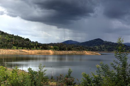 grey water: Rain falls over Wyangala Waters in the Central West region of NSW Australia