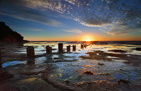 bygone: The golden sun rises on the horizon its first rays of light streaking across the large  wet rockshelf and highlighting ithe  clouds The surface textures of the rockshelf and its puddles reflecting the sky.  The weathered and eroded remnants of a bygone er