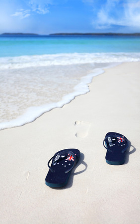 downunder: Australian flag thongs on the beach with footprints leading into the ocean.  Holiday, vacation, travel, leisure, unwind