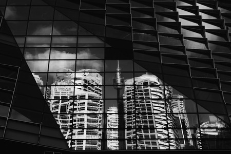SYDNEY, AUSTRALIA - 7 FEBRUARY, 2016;  Distorted reflections of Sydney CBD and Centrepoint Tower within the windows of a new building under construction in Sydney.  Black and White.