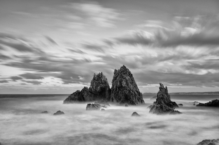 constant: Sunset and long exposure to draw out all the colour in the clouds as the afternoon sun sets to the west at Camel Rock, Australia. The constant waves aruond the rocks blur creating a dreamy effect. that constrasts to the jagged sharpness of the rocks. Stock Photo