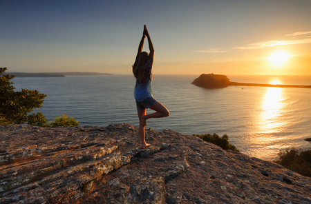 steadiness: A woman standing on a rock looking out to the sea at sunrise doing tree pose variation, yoga, meditation, Vrksasana