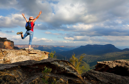 Happy female hiker, traveller, feeling, elation, joy, success, or other positive mood or feeling of wellbeing.  She is high on a rocky outcrop overlooking the Jamison Valley in the Blue Mountains of Australia with Mount Solitary in shade and far in the di