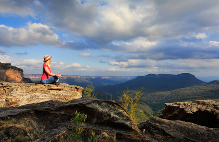 A woman sits peacefully and meditates in a tranquil location on summit of Blue Mountains on a rocky precipice with scenic views. photo