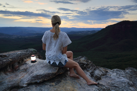 valley below: Woman relaxing perched on a rocky outcrop with views high up in the mountains to the valley below and beyond.  Location:  narrowneck, Blue Mountains, Australia,