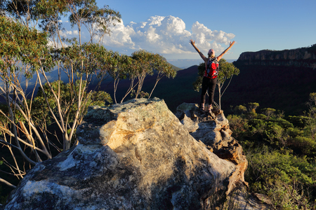 bushwalk: Woman with feeling of exhilaration, standing on top of mountain arms outstretched, with views over the valley and other mountains landscape