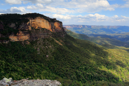 dappled: Views over Jamison Valley, dappled sunlight as the clouds move overhead.  Look closely you can see the tumble down of rocks split off from the main cliff face. Stock Photo
