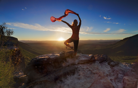 A woman balancing on one leg in mountain landscape, she has her arms outstretched holding sheer flowing fabric backlit by the setting sun moving with the breeze photo