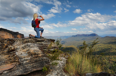 Female hiker bushwalker drinking bottled water at mountain summit with valley views.  Location Blue Mountains Australia photo