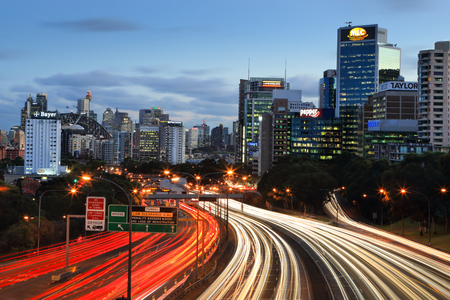 Traffic lights streak along the expressway into and out of the city at dusk.  Sydney icons, like Centrepoint Tower and Sydney Harbour Bridge in view as well as many building of the CBD and North Sydney.