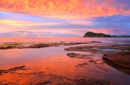 Stunning vivid sunrise over Lion Island from the rocks at Pearl Beach, Australia