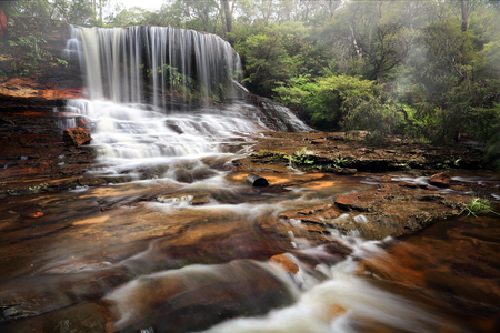 Weeping rock, a tranquil lush waterfall, seen here spilling over and flowing downstream. Blue Mountains Australia