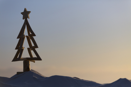 An aussie Christmas.  For Australians Christmas is celebrated in summer.  A driftwood Christmas tree stands in sand in the cool hours of morning just after sunrise Stock Photo
