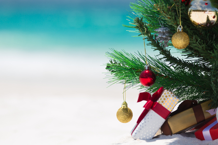 Christmas time spent at the beach in summer. A christmas tree surrounded by presents on a beautiful sandy beach.  Shallow dof with space for copy Stock Photo