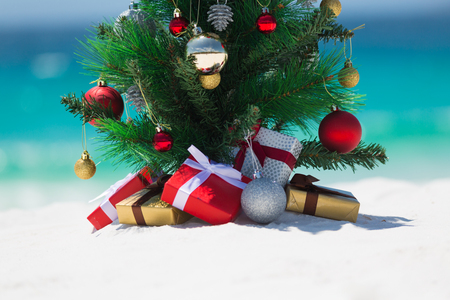 Christmas in some countries is spent in the summer months.  A beautiful christmas tree sits on a white sandy beach under the summer sun.  There are wrapped gifts underneath it.  Space beneath for some copy or message