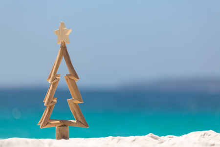 Timber Christmas tree with star sits in pristine white sand with idyllic beach background.  A summer Christmas.   Stock Photo