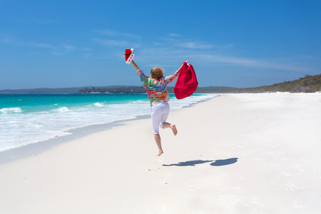 Celebrating Chrismas in Australia, hot sunny days and lazy days down at the beach.  A woman jumps for joy on a beautiful stretch of white sandy beach.  Christmas celebration, Christmas vacation, space for copy Stock Photo