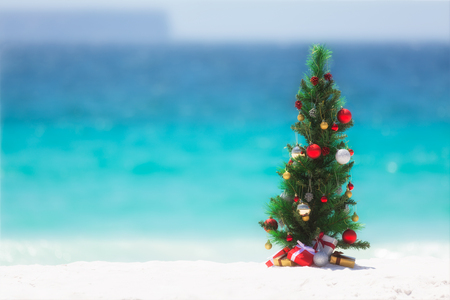 Christmas tree decorated with colourful baubles and presents underneath it, stands on a beautiful sandy beach with background blur of the ocean and sky.  Stock Photo