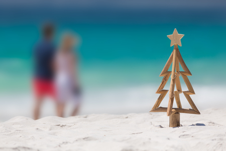 Rustic timber driftwood Christmas tree with star on a white sandy beach with out o f focus ocean snd indistinguishable people strolling by