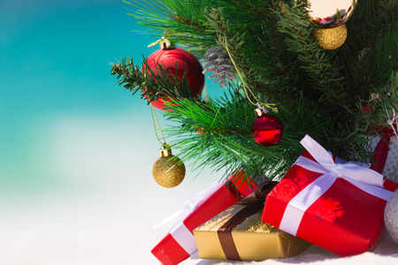 Christmas tree on a beautiful white sandy beach paradise in the summer.  Closeup with background blur suitable copyspace,  Stock Photo