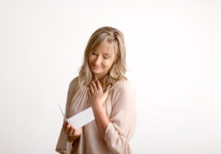 Woman reading a heartfelt message, note, book or card.   She is smiling and has her hand to heart. White background Reklamní fotografie