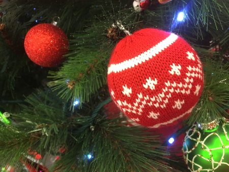 Christmas tree decorations adorn a Christmas tree.  Focus to foreground bauble with a red white winter knit pattern.  Shallow dof.