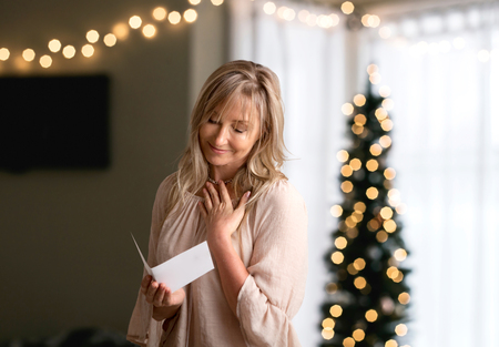 Woman reading a heartfelt message, note, book or card.   She is smiling and has her hand to heart. Stock Photo