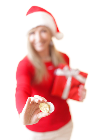 Sydney, Australia - December 17, 2017;  Cheerful confident woman holding two cryptocurrency coins, A Bitcoin and a Litecoin. She is dressed festive and christmassy.   Shallow dof with focus to coins only.