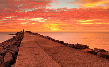 Standing on the breakwall with stunning sunrise skies of vivid reds and oranges.