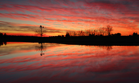 Sensational sunrise in rural Australia with reflections in farm dam Stock Photo