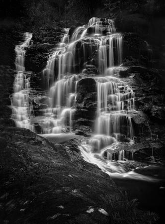 カスケード滝は、谷の床に向かう途中、岩を流れ落ちる。 ロケーション - シルビアフォールズ、ウェントワースフォールズブルーマウンテンオース