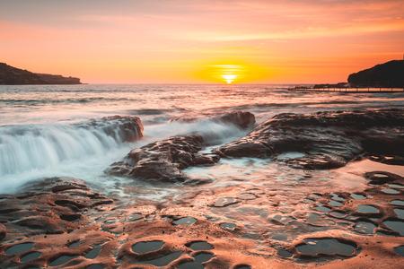 Summer sunrise light up the sky in warm tones and cast its beautiful light over the sea coast.  Australia Stock Photo