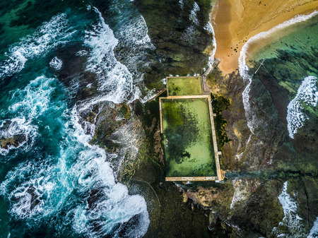 Surrounded by the oceans waves, people do their morning laps at Mona Vale ocean rock pool