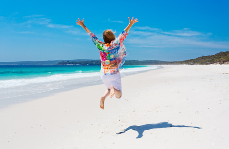 Holiday vacation time. A female jumps for joy on an idyllic beautiful beach