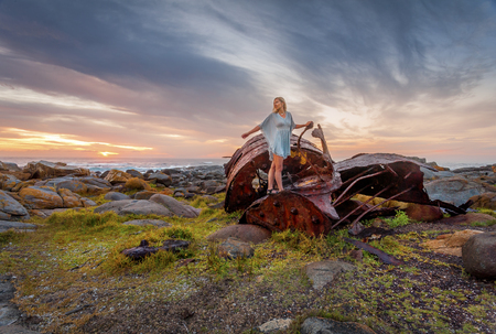 Female explores the rusted remains of a shipwreck parts of which have washed ashore along Australian coastline