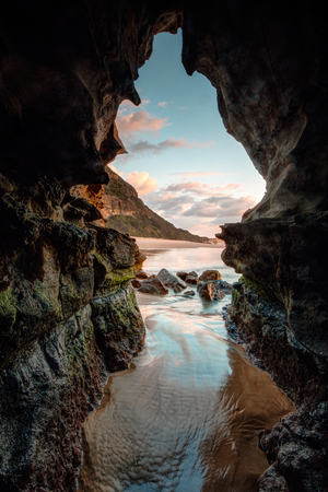 Beach cave with tidal flows and a window to a pretty sunrise Banque d'images