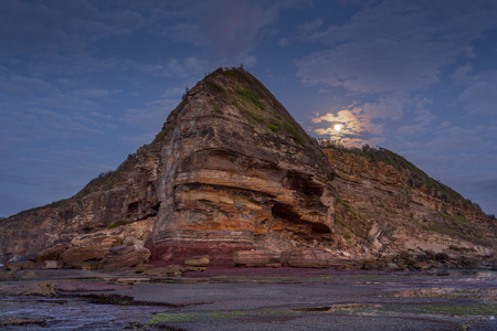 Cool dawn hues as the moon sets behind Turimetta headland Banque d'images