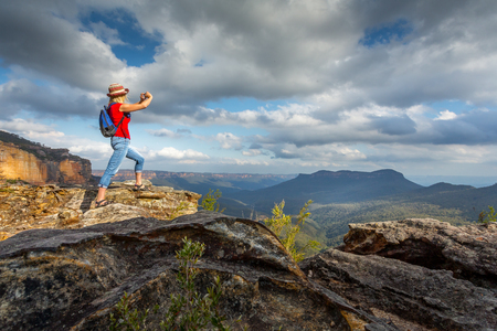 Tourist taking photos from cliff tops of stunning panoramic Blue Mountain vistas