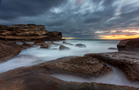 A 70 second long exposure on the exposed lower rock shelf and ocean waves at Potter Point Kurnell with silky wave motion that take on a mystical foggy glow  around the rocks and clouds flicking in various directions as the wind took them over the exposure time. Banque d'images