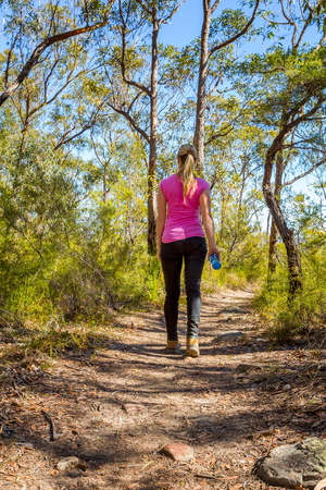Female walking along a bush track among nature.  She is carrying a water bottle in one hand