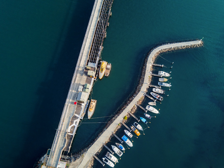 Various boats of different shapes and sizes moored at a curved pier in Port Kembla